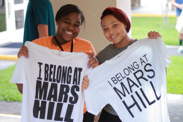 Two students hold Tshirts