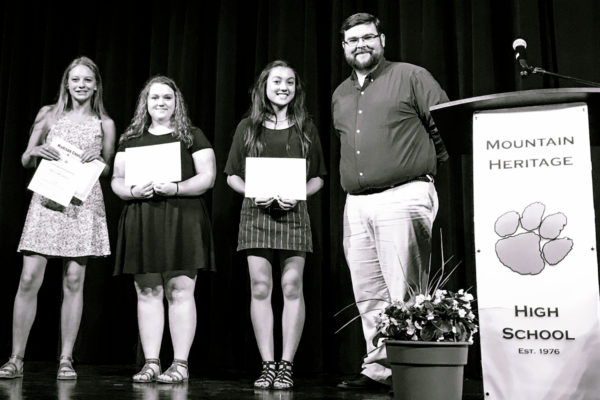 Mars Hill University admissions counselor Andrew McKinney presents scholarships to (l-r) Alyssa Jamerson, Ashley Ruff, and Hannah Robinson. Not pictured: Kelsy Sullivan.