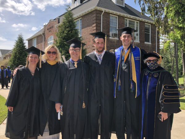 5 graduates in robes and one faculty member at graduation