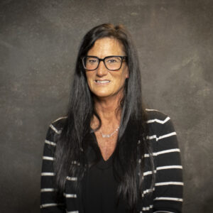 Photo of adult student with dark hair wearing glasses and a black and white shirt.